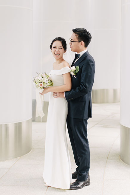 bride and groom laughing holding bouquet