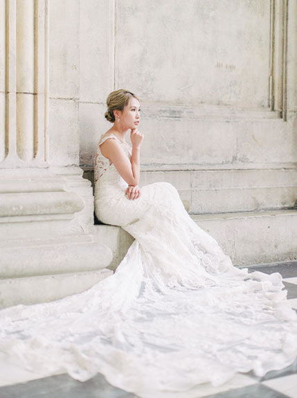 bride poses thoughtfully in wedding dress