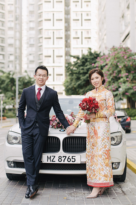 bride and groom pose infront of wedding care