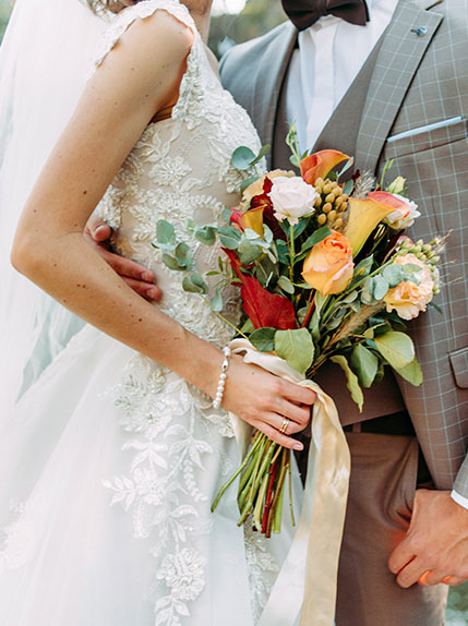 photo of bride holding bouquet with groom