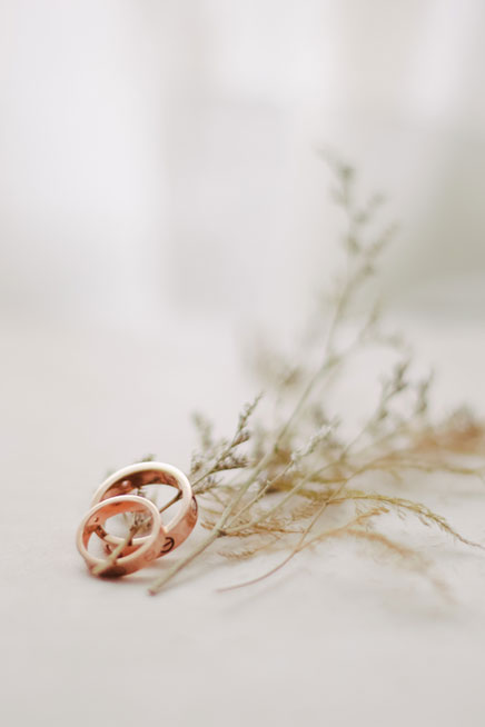 two wedding rings resting on flowers