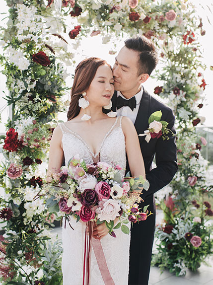 photo of bride and groom infront of wedding arch