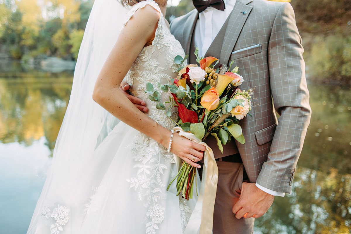 bride holds colorful floral bouquet with groom