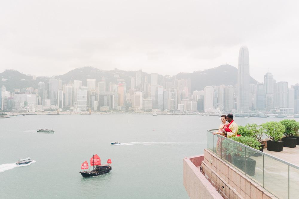 couple standing on outdoor balcony looking over hong kong skyline