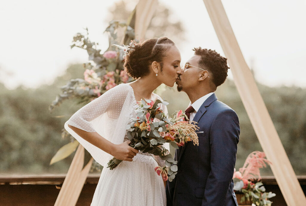 bride and groom kissing holding bouquet