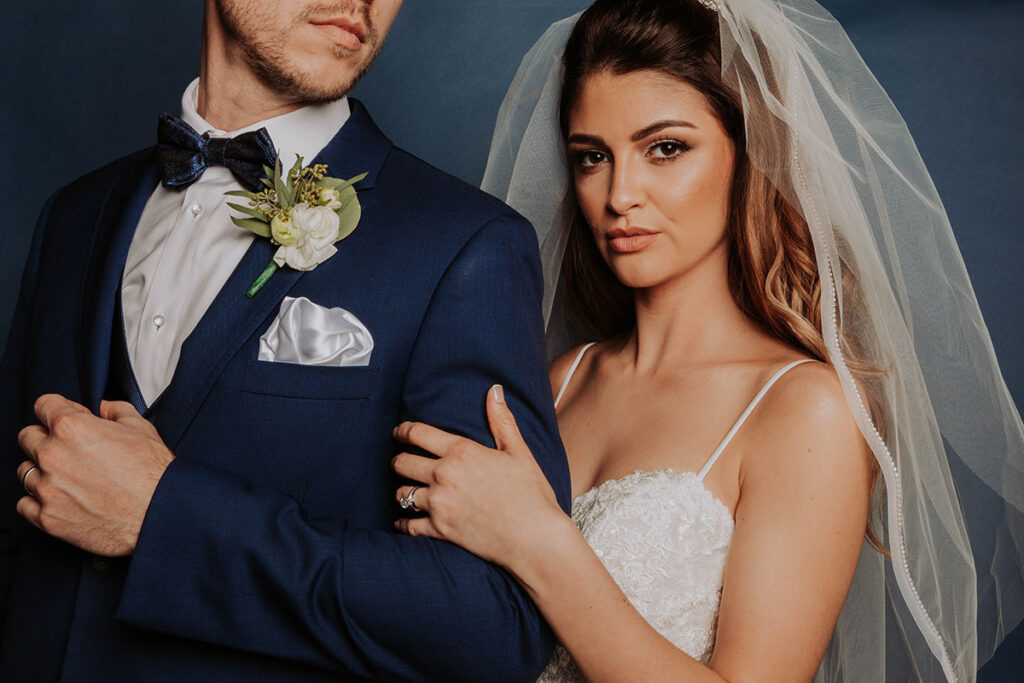 bride holds grooms arm during wedding shoot