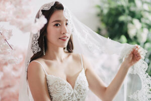 bride holds wedding veil up during pre wedding