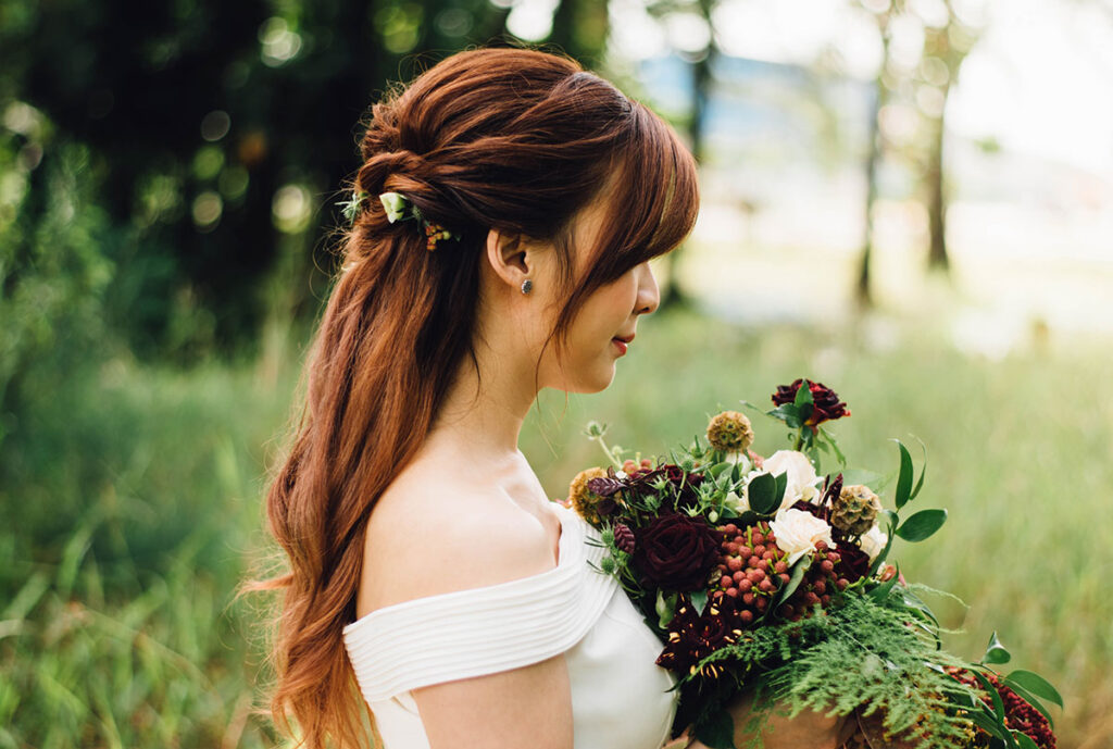 bride looks into bouquet surrounded by woodland