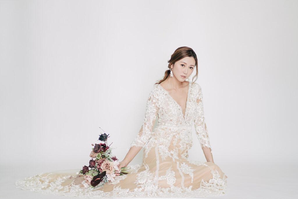 hong kong bride sits on floor in wedding gown
