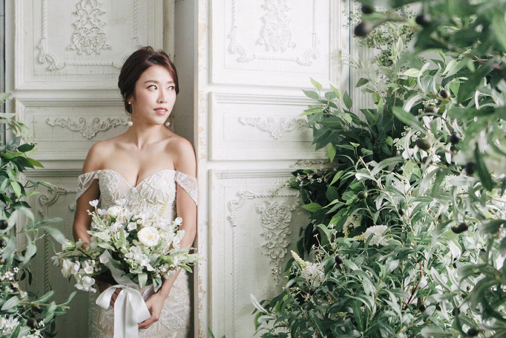 bride poses with should drop wedding dress