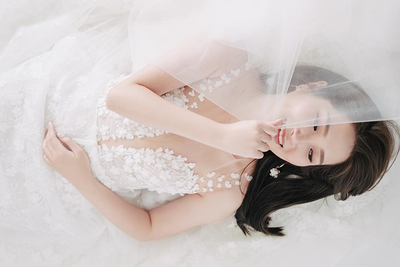 bride lies on the floor holding wedding veil