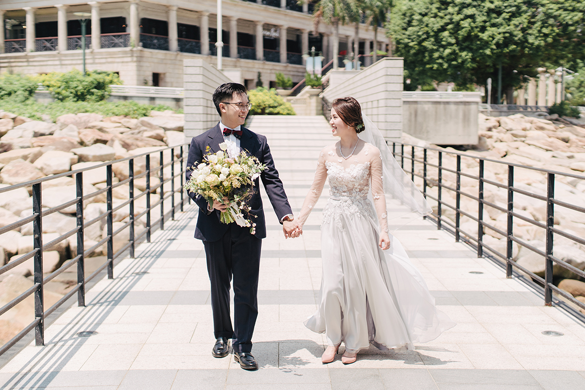 groom holds bouquet while holding hands with bride in front of murray house